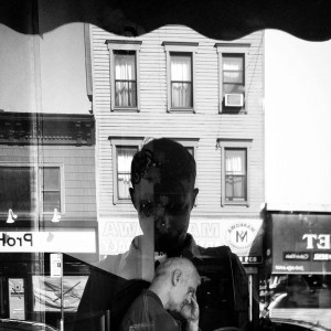 Nathan Fitch in one of his selfies from his Photography Project, where he is taking photos outside of a window with a forlorn man inside the shop