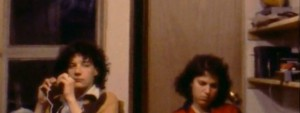 Still from the film showing a guy and girl sitting against a wall