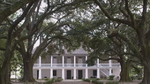 Still from film that shows large white house under canopy of trees