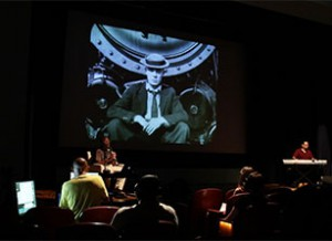an audience watching a black and white film of a man in a bowler hat