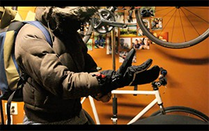 Still from the film showing a person putting on a glove while sitting on a bike